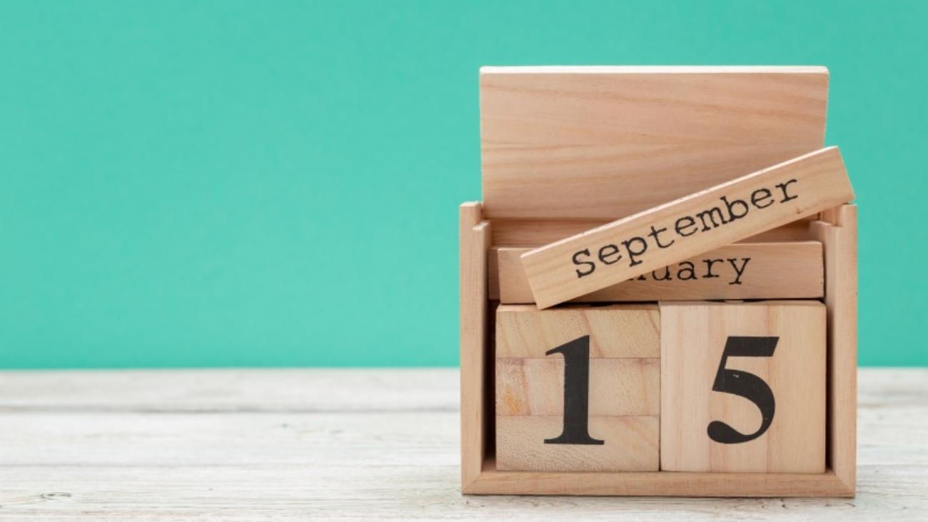 wooden cube shape calendar for september 15 on wooden tabletop